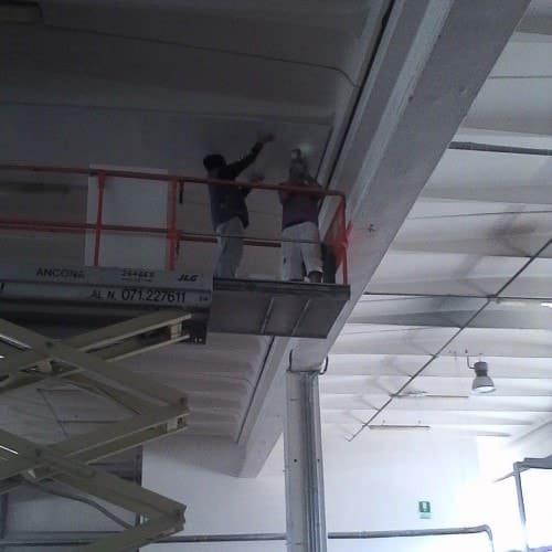 Piattaforma elevatrice industriale utilizzata per tinteggiare il soffitto interno del complesso industriale
