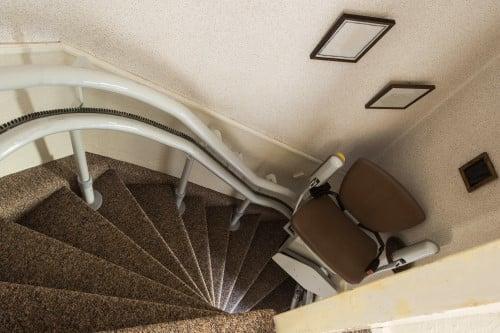 montascale a poltroncina installato su una scalinata curva con scale a forma triangolare