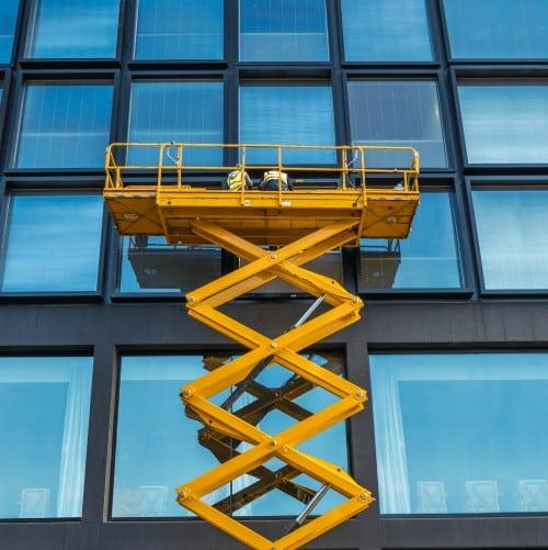 piattaforma elevatrice industriale a pantografo utilizzata per raggiungere i piani più alti dell'edificio in vetro