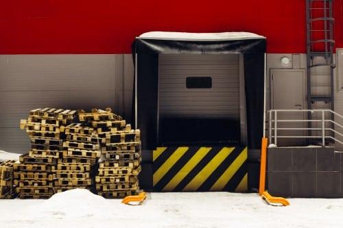 piattaforma elevatrice industriale per lo stoccaggio di merci con segnale di avvertimento con linee diagonali giallo e nere