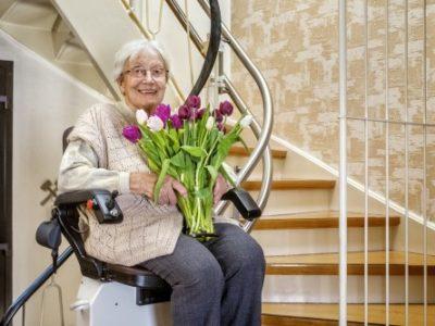 signora sorridente su un montascale a poltroncina con fiori in mano