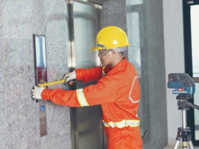 tecnico ascensorista verifica le quote della bottoniera di piano