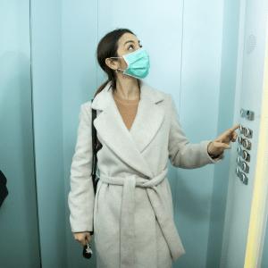 donna in ascensore con la mascherina da infermiere durante corona vrisu