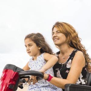 scooter elettrico per disabili guidato dalla mamma con la figlia