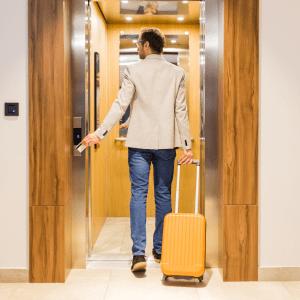 uomo entra in ascensore con valigia